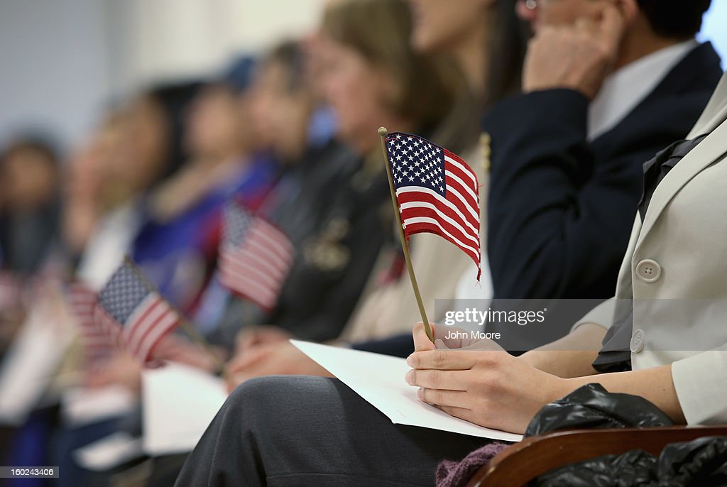 Immigrants hold flags while waiting for a naturalization ceremony to become U.S. citizens at the district office of U.S. Citizenship and Immigration Services (USCIS) on January 28, 2013 in Newark, New Jersey. Some 38,000 immigrants became U.S. citizens at the Newark office alone in 2012.