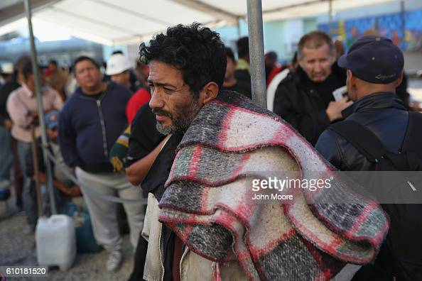 Immigrants many of them deportees from the United States await breakfast at a soup kitchen on September 24 2016 in Tijuana Mexico The center called...