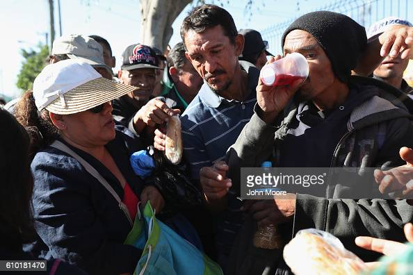 Immigrants many of them deportees from the United States take leftovers from a soup kitchen on September 24 2016 in Tijuana Mexico The center called...