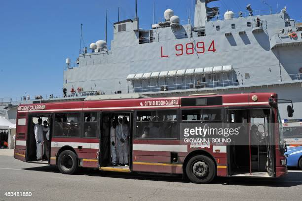Immigrants part of a group of more than 1700 people wait in a bus after they disembarked from the Italian military ship 'San Giusto' on August 11...