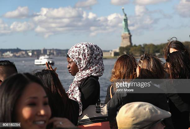 Immigrants pass near the Statue of Liberty while in route to Ellis Island for a naturalization ceremony on September 16 2016 in New York City The...