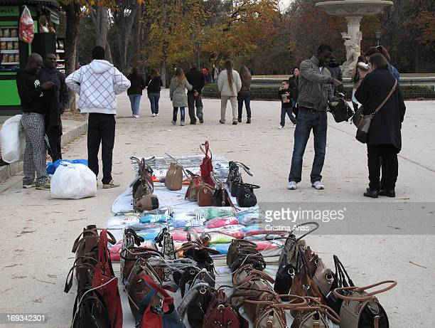 Immigrants selling handbags and other items of counterfeit luxury brands in the Retiro Park in Madrid Spain