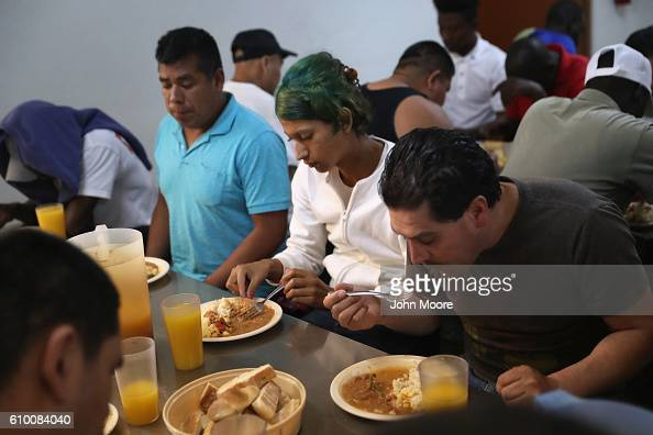 Immigrants sit down for dinner at the Casa Del Migrante shelter on September 23 2016 in Tijuana Mexico The shelter run by Catholic priests is part of...