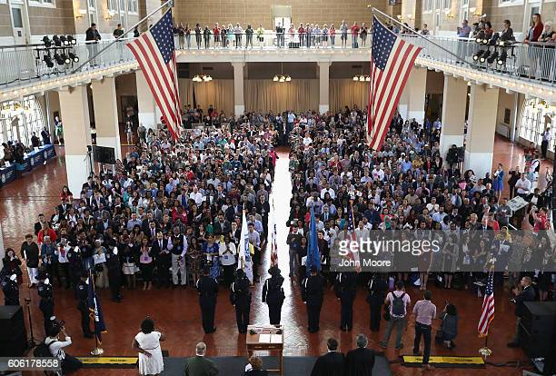 Immigrants stand for the US national anthem during a naturalization ceremony in the Great Hall of Ellis Island on September 16 2016 in New York City...