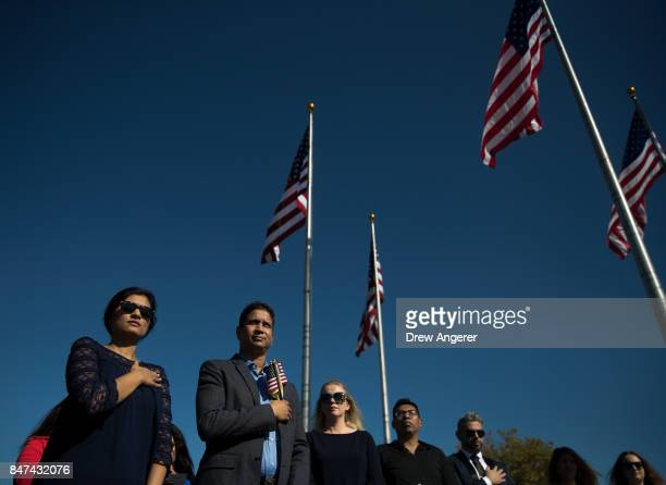 Immigrants stand for the US National Anthem during a naturalization ceremony at Liberty State Park September 15 2017 in Jersey City New Jersey To...
