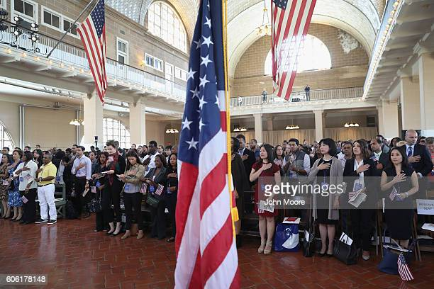 Immigrants take part in a naturalization ceremony in the Great Hall of Ellis Island on September 16 2016 in New York City The ceremony marked US...