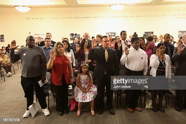 Immigrants take the oath of citizenship at a special Valentine's Day naturalization ceremony for married couples on February 14 2013 in Tampa Florida...