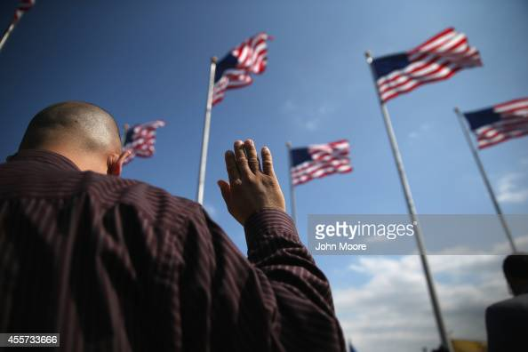 Immigrants take the oath of citizenship to the United States during a naturalization ceremony at Liberty State Park on September 19 2014 in Jersey...