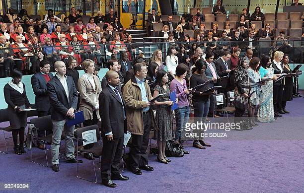 Immigrants to the United Kingdom take an oath before being presented with a certificate of citizenship by the London Mayor Boris Johnson during a...