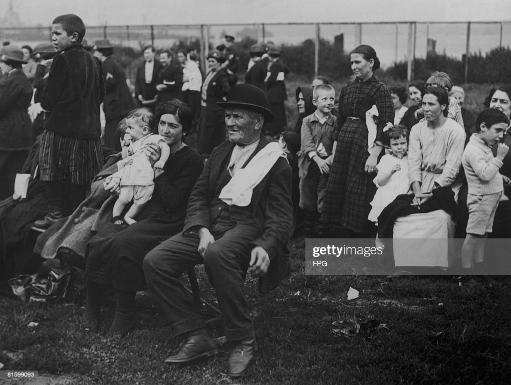 Immigrants to the US on Ellis Island New York circa 1920 The woman and child in the foreground are from Italy while the man in the bowler hat is Irish