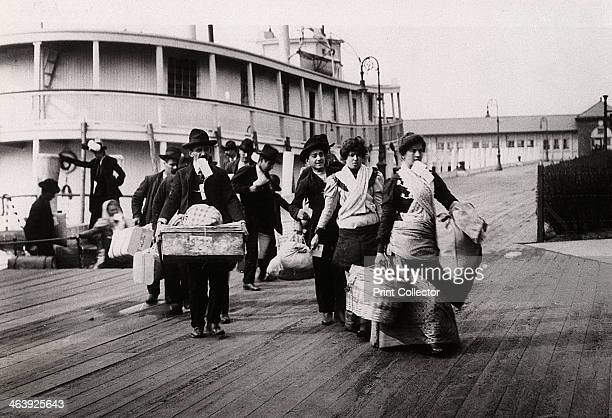 Immigrants to the USA landing at Ellis Island New York c1900 They head for the processing centre each carrying a paper with an entry number which...