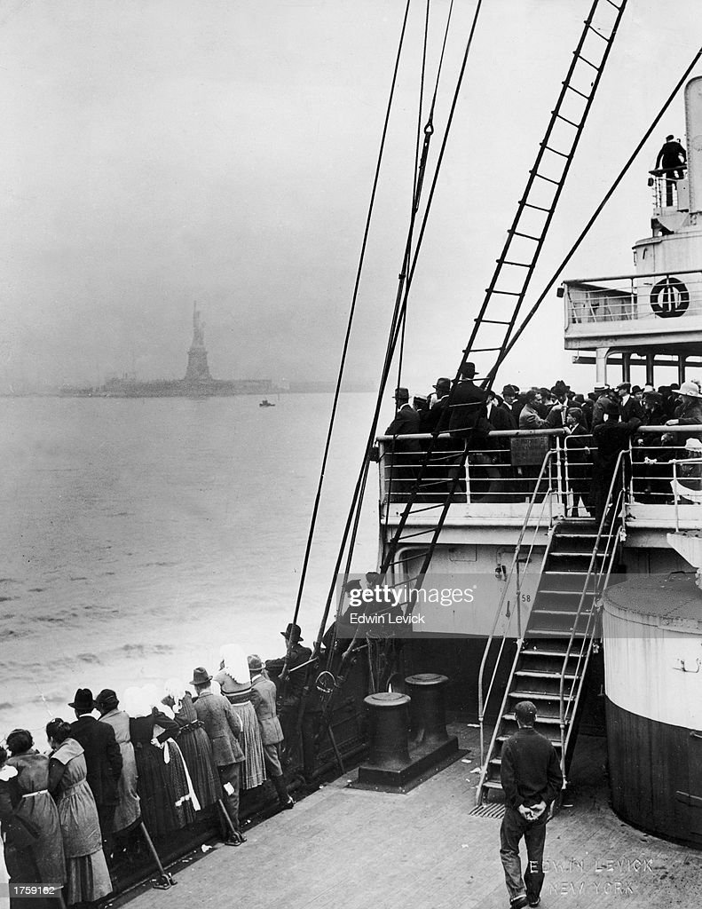 Immigrants view the Statue of Liberty while entering New York harbor aboard an ocean liner en route to Ellis Island, New York City, 1910s.