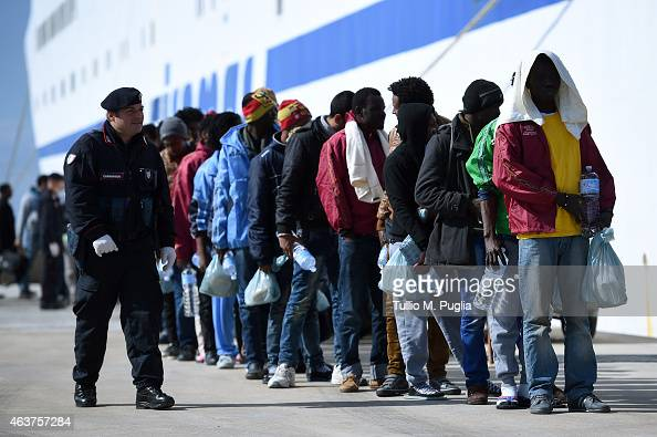 Immigrants wait to board a ship on February 18 2015 in Lampedusa Italy Hundreds of migrants have recently arrived in Lampedusa fleeing the attacks by...