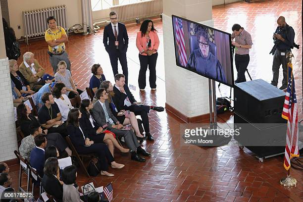 Immigrants watch as US Supreme Court Associate Justice Sonia Sotomayor gives a taped address at a naturalization ceremony on Ellis Island on...