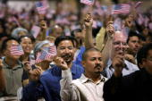 Immigrants wave flags after being sworn in as US citizens in naturalization ceremonies on July 26 2007 in Pomona California Some of the 6000 people...