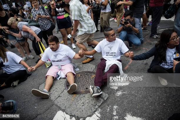Immigration activists protesting the Trump administration's decision on the Deferred Action for Childhood Arrivals program sit in the street and...