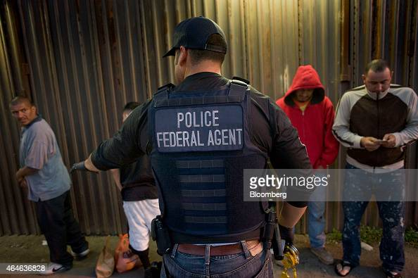A US Immigration and Customs Enforcement agent directs a group of undocumented men being deported to Mexico at the USMexico border in San Diego...