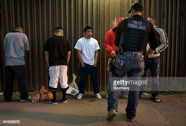 A US Immigration and Customs Enforcement agent removes handcuffs from undocumented men being deported to Mexico at the USMexico border in San Diego...