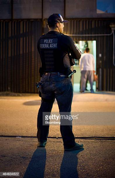 A US Immigration and Customs Enforcement agent waits as an undocumented man is received by Mexican immigration at the USMexico border in San Diego...