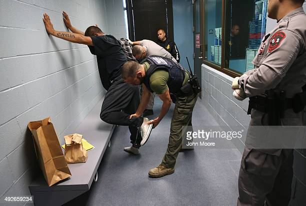 S Immigration and Customs Enforcement agents frisk a detained immigrant at a processing center on October 14 2015 in Camarillo California ICE builds...