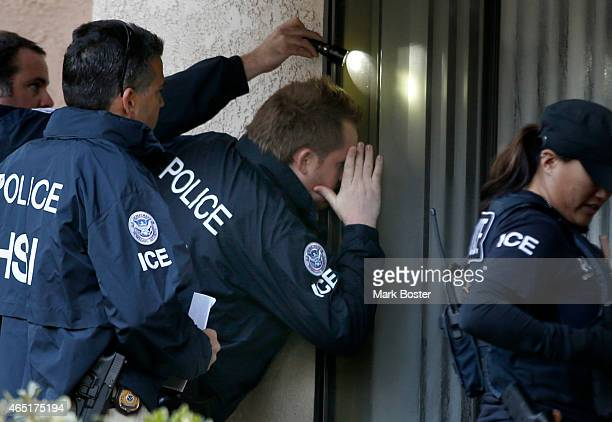 Immigration and Customs Enforcement agents from the Department of Homeland Security look into the window of an apartment while executing search...