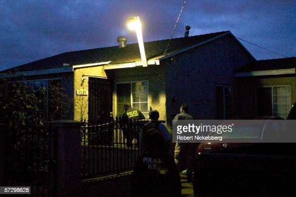 US Immigration and Customs Enforcement agents in a predawn raid approach a house in San Diego California in search of a Mexican national who has...