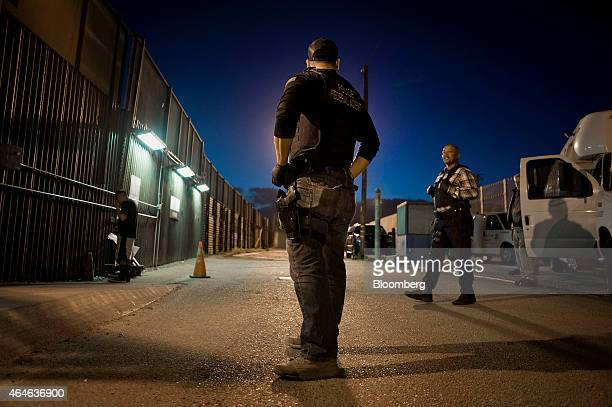 US Immigration and Customs Enforcement agents speak as an undocumented man is being deported to Mexico at the USMexico border in San Diego California...