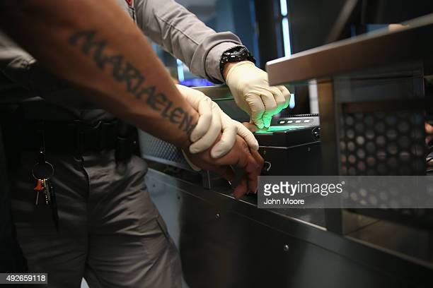 S Immigration and Customs Enforcement contractor fingerprints a detained immigrant at a processing center on October 14 2015 in Camarillo California...