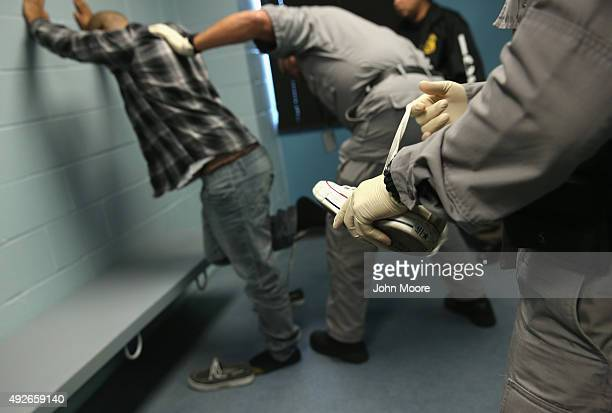 S Immigration and Customs Enforcement contractor removes the shoelaces from a detained immigrant at a processing center on October 14 2015 in...