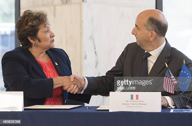 US Immigration and Customs Enforcement Director Sarah Saldana shakes hands with Frederic Dore Deputy Chief of Mission of the French Embassy after...