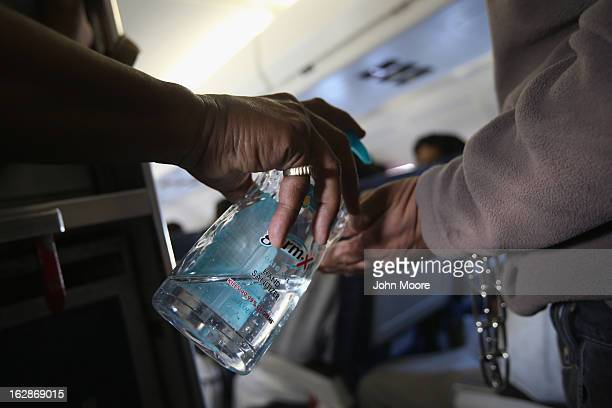 S Immigration and Customs Enforcement security contractor squirts hand sanitizer onto the hands of a Honduran immigration detainees before deporting...