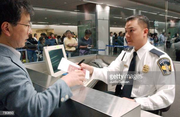 S immigration inspector Tron Nguyen processes an unidentified man going through customs at San Francisco International Airport June 14 2002 in...