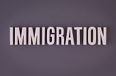 Immigration lettering sign made with colorful background and white ceramic letters.