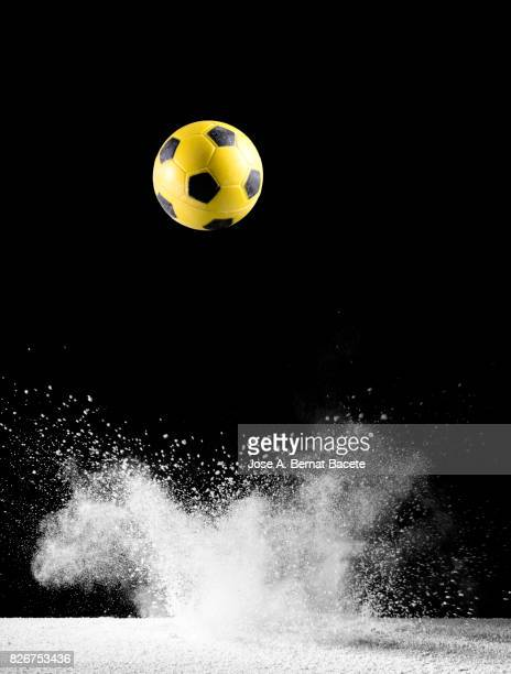 Impact and rebound of a ball of football  on a surface of land and powder on a black background