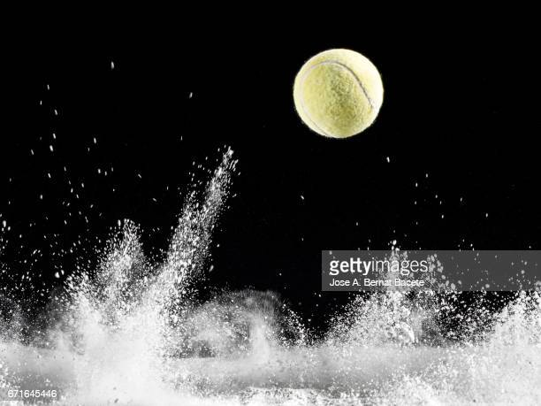 Impact and rebound of a ball of tennis on a surface of land and powder on a black background