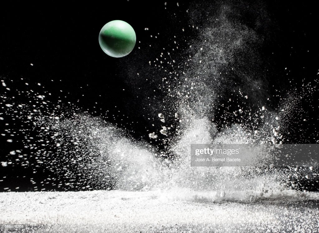Impact and rebound of a ball  on a surface of land and powder on a black background : Stock Photo