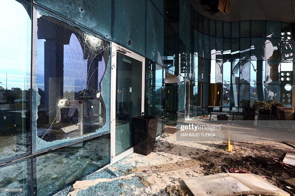 Impact holes are seen on glass doors at the entrance of Tripoli's central Corinthia Hotel on January 28 where gunmen blew themselves up after...