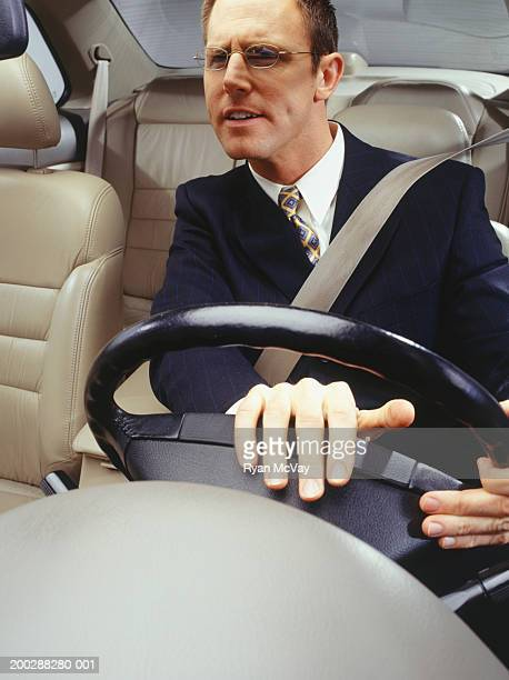 Impatient businessman pushing horn in car