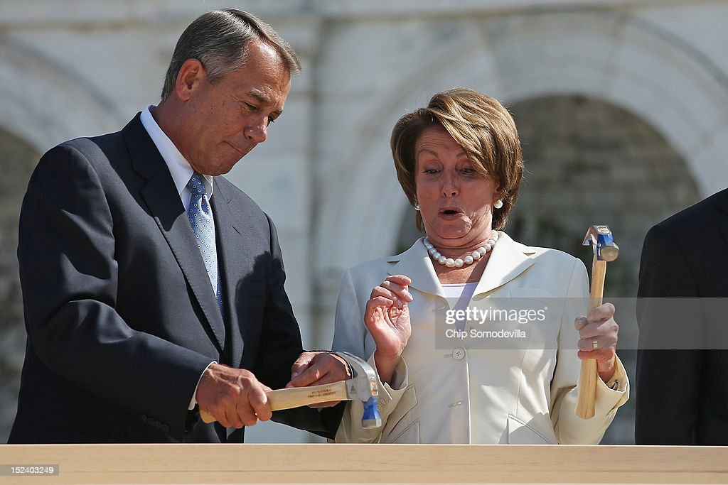 Impatient with how long it was taking House Minority Leader <a gi-track='captionPersonalityLinkClicked' href=/galleries/search?phrase=Nancy+Pelosi&family=editorial&specificpeople=169883 ng-click='$event.stopPropagation()'>Nancy Pelosi</a> (D-CA) (R) to drive a nail, Speaker of the House <a gi-track='captionPersonalityLinkClicked' href=/galleries/search?phrase=John+Boehner&family=editorial&specificpeople=274752 ng-click='$event.stopPropagation()'>John Boehner</a> finishes the job with one stroke during the 'First Nail' ceremony, signifying the start of construction of the 2013 Inaugural Platform on the West Front of the U.S. Capitol September 20, 2012 in Washington, DC. The winner of the November 6 presidential election will be sworn in on the platform on January 21, 2013.