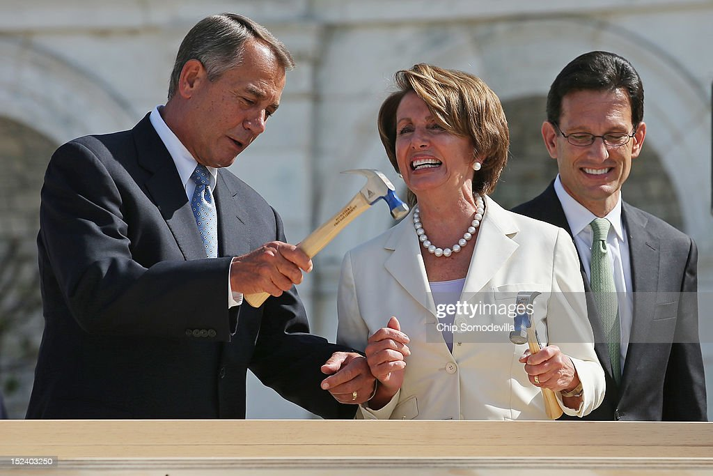 Impatient with how long it was taking House Minority Leader <a gi-track='captionPersonalityLinkClicked' href=/galleries/search?phrase=Nancy+Pelosi&family=editorial&specificpeople=169883 ng-click='$event.stopPropagation()'>Nancy Pelosi</a> (D-CA) (R) to drive a nail, Speaker of the House <a gi-track='captionPersonalityLinkClicked' href=/galleries/search?phrase=John+Boehner&family=editorial&specificpeople=274752 ng-click='$event.stopPropagation()'>John Boehner</a> finishes the job with one stroke during the 'First Nail' ceremony, signifying the start of construction of the 2013 Inaugural Platform on the West Front of the U.S. Capitol September 20, 2012 in Washington, DC. House Majority Leader <a gi-track='captionPersonalityLinkClicked' href=/galleries/search?phrase=Eric+Cantor&family=editorial&specificpeople=653711 ng-click='$event.stopPropagation()'>Eric Cantor</a> (R-VA) is at right. The winner of the November 6 presidential election will be sworn in on the platform on January 21, 2013.