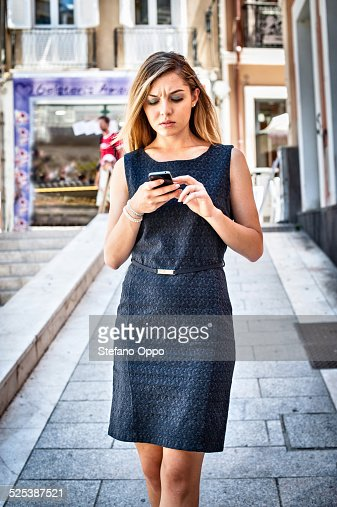 Impatient young woman texting on smartphone on city street