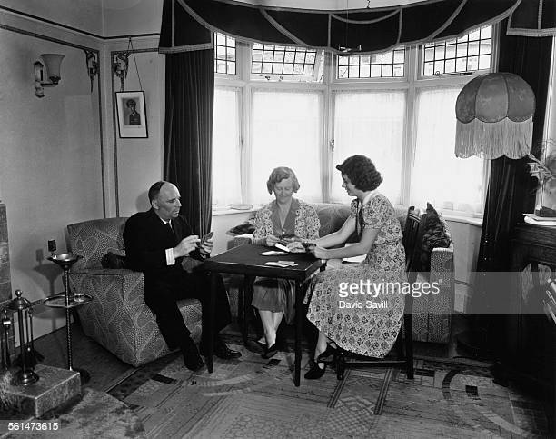Imperial Airways airline pilot Captain Frederick Dismore playing cards with his wife and daughter at their home in Thornton Heath London 7th August...