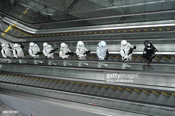 Imperial Stormtroopers and a TIE pilot from the Star Wars film franchise travel up an escalator during a promotional event at the Changi...