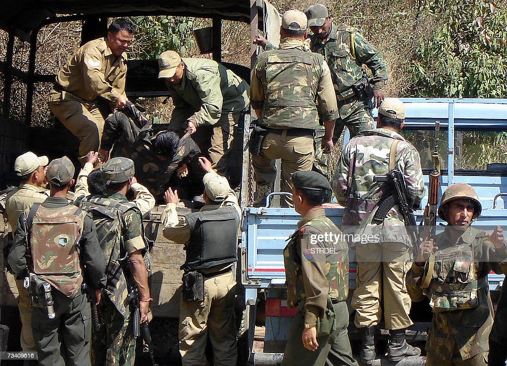Indian army personnel lift the body of a policeman from a truck in the grounds of The Civil Hospital in Imphal 24 February 2007 after his death in an...