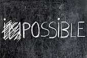 Impossible becomes possible handwritten with white chalk on dirty blackboard