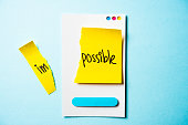 Impossible is possible note with paper smart phone concept on blue background.