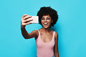 Attractive young African woman smiling and taking selfie while standing against blue background
