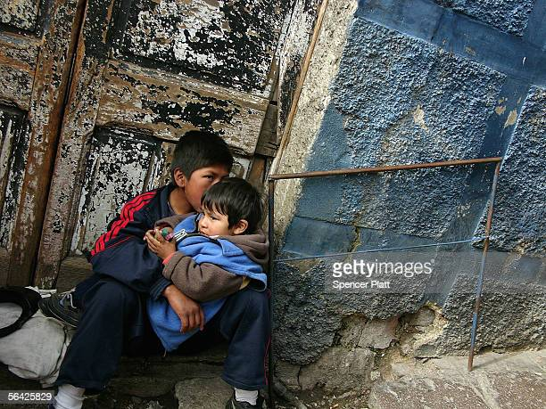 Impoverished Bolivian children sit on a street corner December 13 2005 in La Paz Bolivia Bolivia South Americas poorest country is about to face a...
