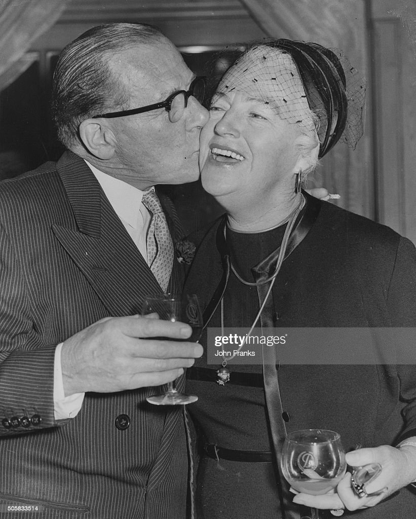 Impresario Jack Payne kissing actress Gracie Fields on the cheek as they attend a luncheon to celebrate the release of her autobiography 'Sing As We...