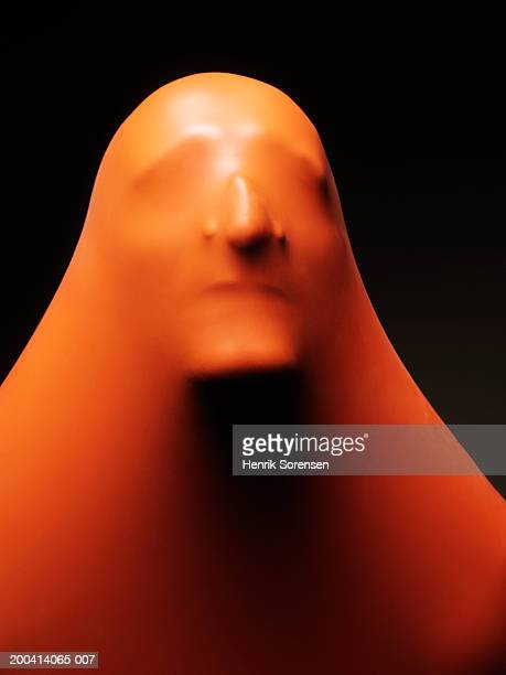 Impression of man's face through orange rubber, close-up